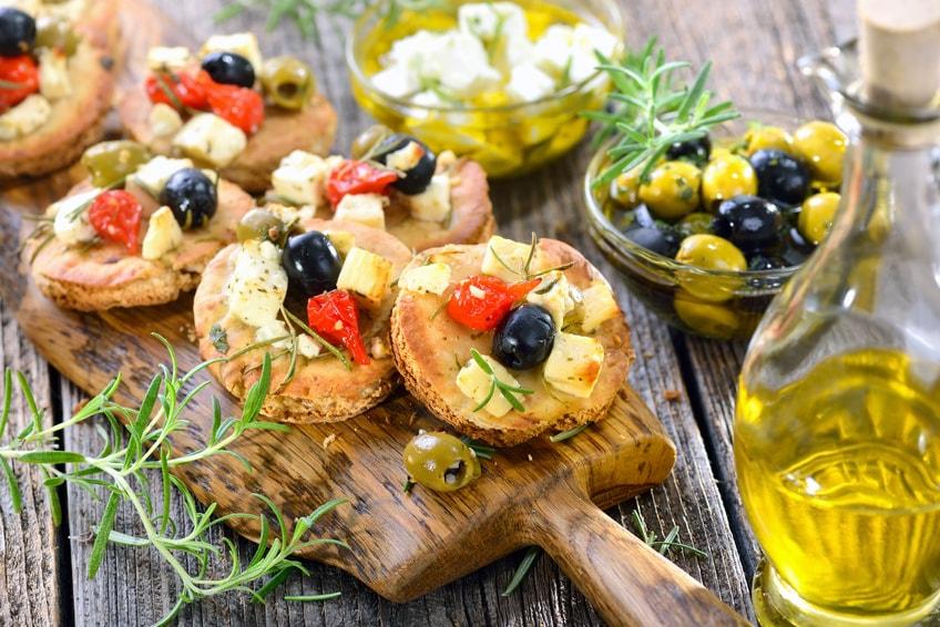 Warme griechische Vorspeise: Überbackene Pita-Brötchen mit Feta, Oliven, Minipaprika und Olivenöl